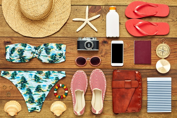 Full frame shot of summer vacation accessories. Directly above shot of travel and beach equipment flat lay. They are arranged on wooden floor.