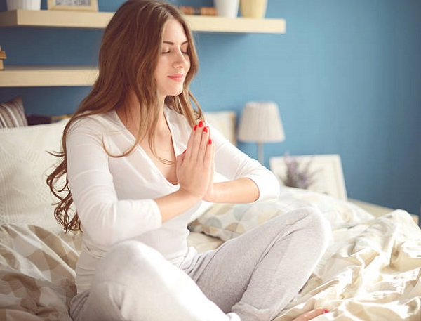 young woman meditating in the bedroom on the bed
