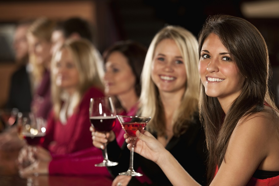Smiling Young Female Friends Enjoying Drinks